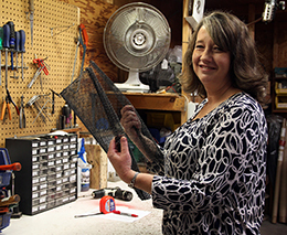 photo of Condar employee Karen holding a fireplace mesh screen