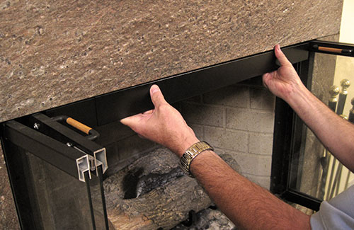 Photo of a Rod and Valance kit being installed on a fireplace.